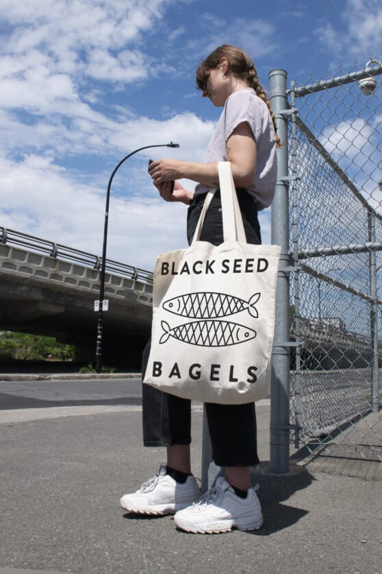 a woman carries a black seed bagels totebag outside