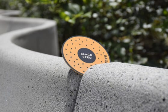 a sticker designed for black seed bagels on a stone wall