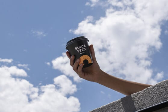 a hand holding a black seed bagels coffee cup against a blue sky