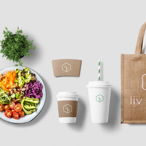 coffee cups, cartons, and tote bags with the liv salad branding