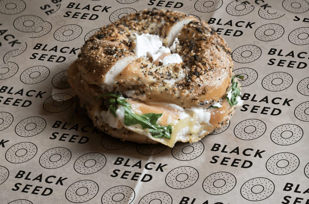 an everything bagel with cream cheese on custom wax paper