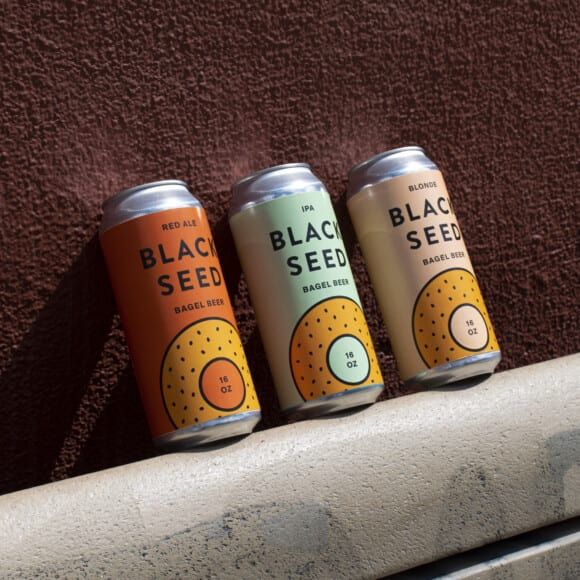 three cans of black seed bagels branded beer leaning against a wall