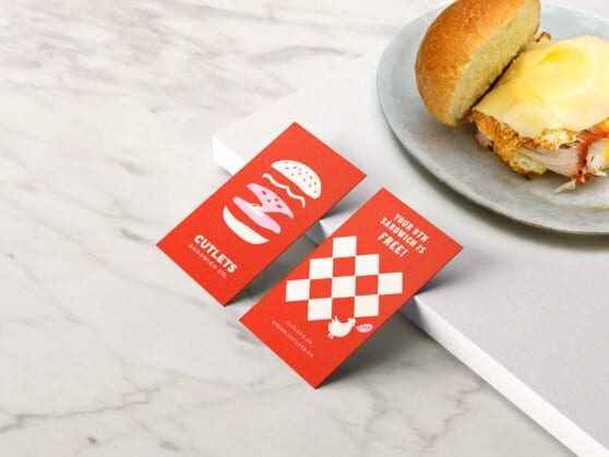 Cutlets business cards next to a sandwich