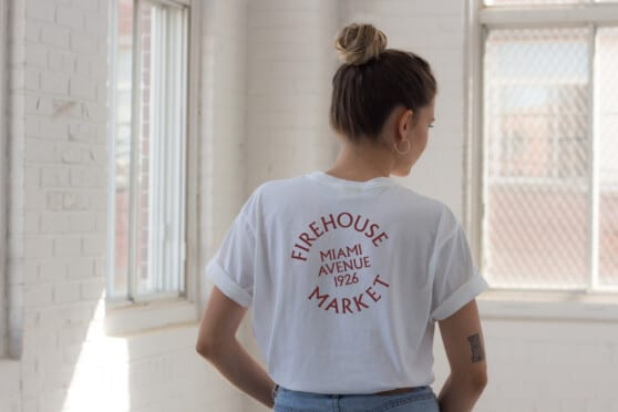 woman wears a firehouse market t-shirt