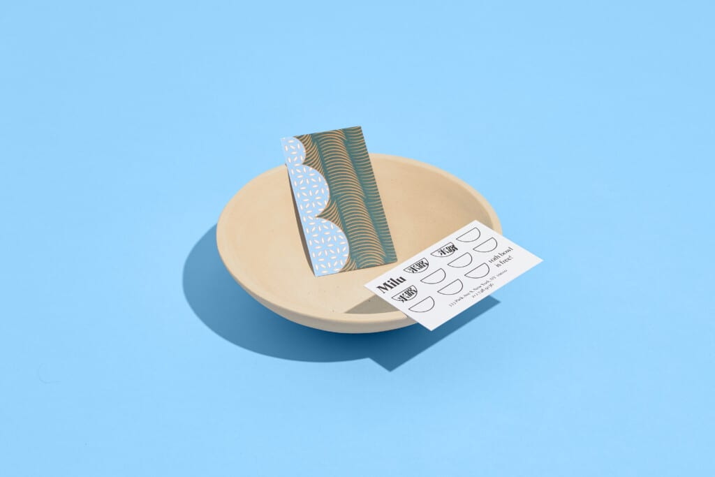 milu business cards in a bowl on blue background